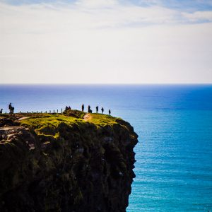 Hikers peering over the edge of the Cliffs of Moher in County Clare, Ireland on a sunny day