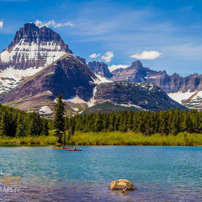 Two kayakers on Swiftcurrent Lake on a sunny day in Glacier National Park, Montana