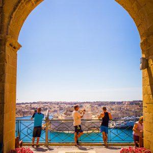 Tourists taking photos in the Upper Barrakka Gardens of Valletta, Malta on a sunny day