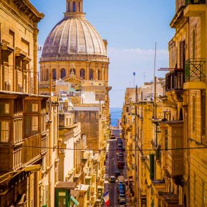 The dome of the Basilica of Our Lady of Mount Carmel viewed down a steep, narrow street in Valletta, Malta on a sunny day