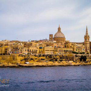 The historic skyline of Valletta, Malta viewed from across the bay with the dome of Our Lady of Mount Carmel visible on a cloudy day