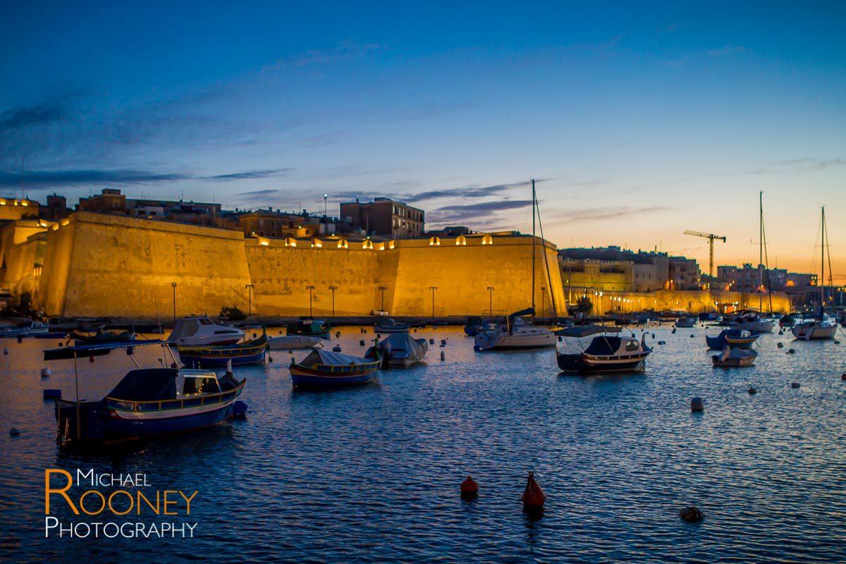 birgu malta walls fortification citadel lit dusk boats harbor bay