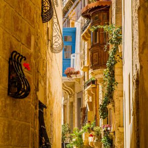 A narrow alley with window planter boxes in the historic city of Mdina, Malta on a sunny day