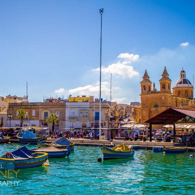 Fishing boats in front of the Parish Church of Our Lady of Pompei in the village of Marsaxlokk, Malta on a sunny day