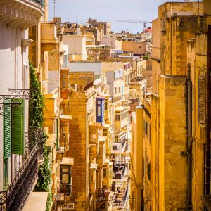 A steep and narrow street in historic Valletta, Malta on a sunny day