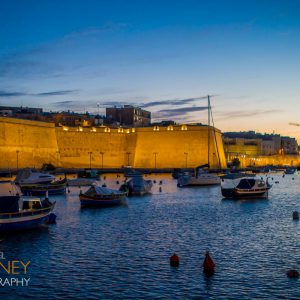 The historic walls of Birgu, Malta lit at dusk as viewed from across the harbor