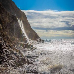 Waves crash onto rocks below Alamere Falls