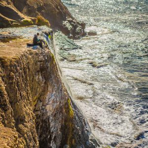 A couple sits atop Alamere Falls in Point Reyes National Seashore