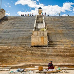 A woman at the foot of the Buudha Dordenma statue entrance stairway in Thimphu, Bhutan