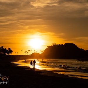 People in silhouette at sunset on Nacpan Beach in El Nido, Palawan, Philippines