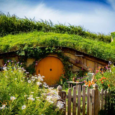 A hobbit hole with an orange door at the Hobbiton movie set near Matamata, New Zealand on a sunny day