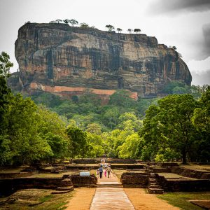Tourists walking down the entrance path as Sigiriya Fortress looms above them on a cloudy morning in Sri Lanka