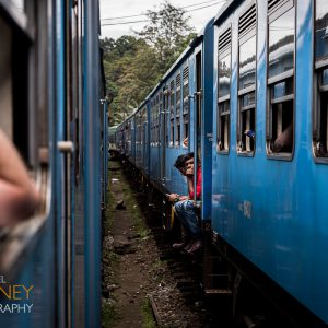 Two trains pass one another on the way to Ella, Sri Lanka as two men sit in the doorway