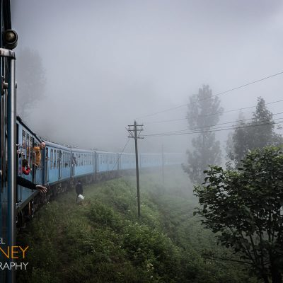 Blue train to Ella rounds a curve in Sri Lanka's highland tea country in the fog