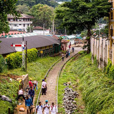 Students walk along the railroad tracks outside of Kandy Railway Station in Sri Lanka