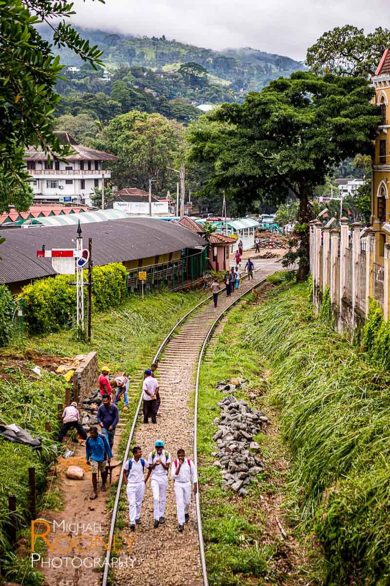 students railroad train tracks kandy sri lanka