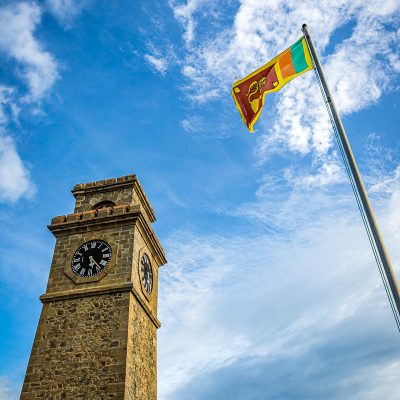 The clocktower and Sri Lankan flag at the Galle Fort on a sunny day